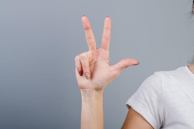 Main féminine dans le poing montrant trois doigts isolés sur gris