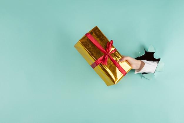 Une main féminine dans un trou déchiré sur fond bleu tient une boîte dorée avec un cadeau. la main à travers du papier déchiré