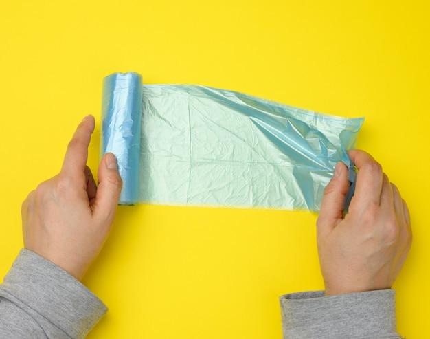 Main féminine déroule un sac en plastique bleu pour les ordures, surface jaune, vue du dessus