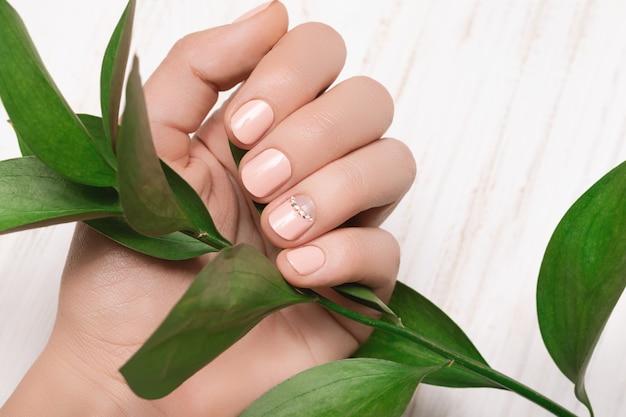 Main féminine avec un design d'ongle rose. main de femme rose avec feuille verte sur une surface blanche.
