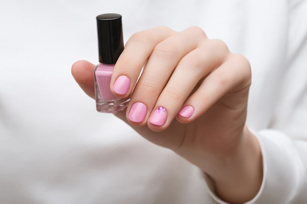 Main féminine avec un design d'ongle rose tenant une bouteille de vernis à ongles