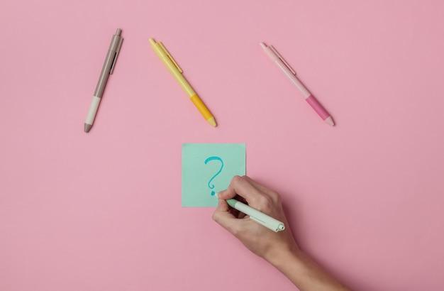 Main féminine dessine un stylo avec un point d'interrogation sur un morceau de papier mémo