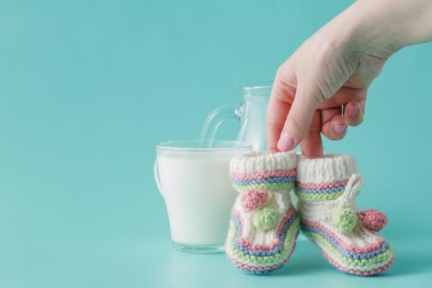 Main féminine détient de petites chaussures de bébé