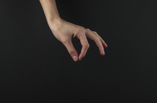 La main féminine avec les doigts tient quelque chose sur fond noir.