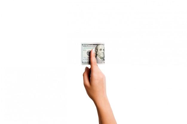 Main féminine donnant de l'argent sur fond isolé blanc. vue de dessus des billets en dollars. concept de pot-de-vin. concept de dette et de prêt