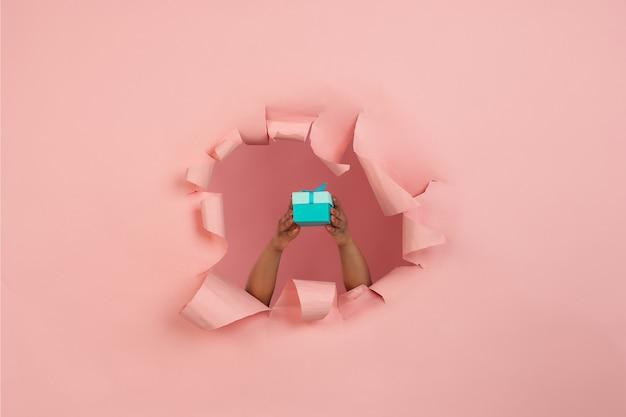 Main féminine donnant un cadeau dans un trou de papier rose corail déchiré