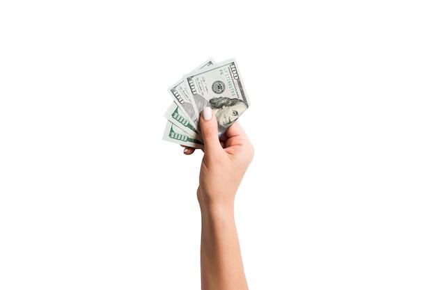 Main féminine donnant un paquet de billets d'un dollar sur une surface isolée blanche
