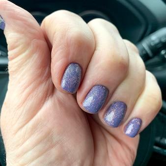 Main féminine avec du vernis à ongles brillant en voiture