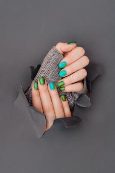 Une main féminine avec du vernis à ongles coloré vert menthe de printemps sur la tenue d'une brindille sur un fond vert