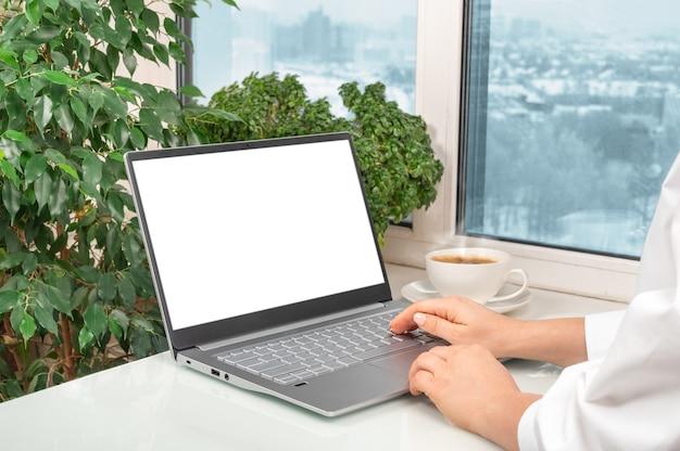 Main féminine écran blanc à l'aide d'un ordinateur portable. contactez les informations de recherche d'entreprise sur le bureau au bureau à domicile.