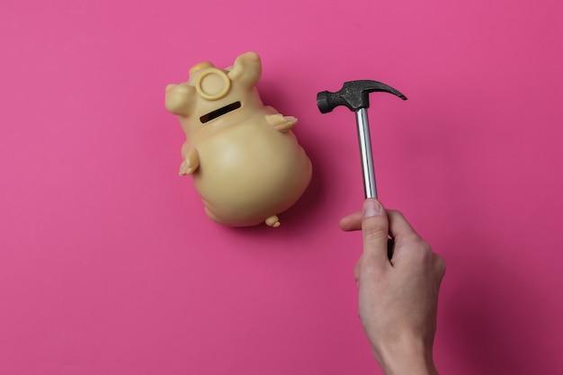 Main féminine écrase une tirelire avec un marteau sur fond rose concept minimaliste