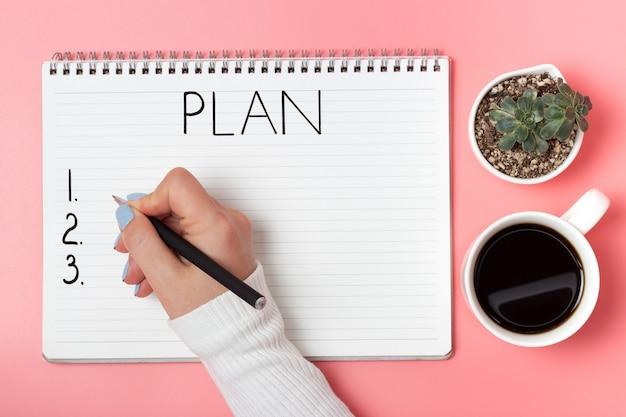 Main féminine écrit dans le bloc-notes du plan sur un fond rose