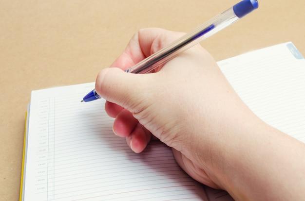 Une main féminine écrit dans un cahier et prend des notes, des plans de la journée, une liste de courses, un gros plan