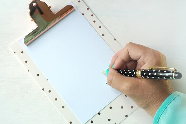 Une main féminine écrit avec un stylo à bille sur une feuille de papier vierge dans un presse-papiers.
