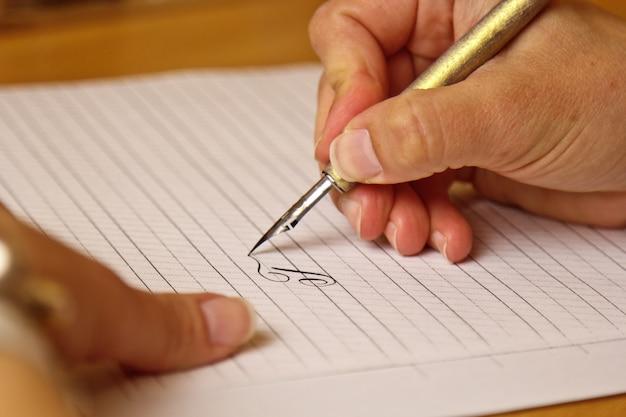 Une main féminine écrit avec un stylo à encre sur une feuille de papier blanche avec des rayures.