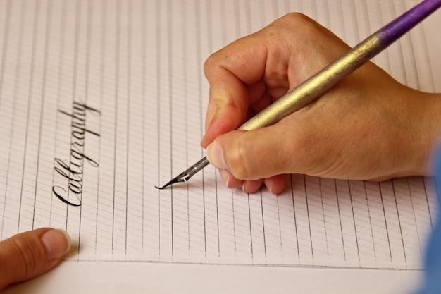 Une main féminine écrit avec le stylo encre le mot calligraphie sur une feuille de papier rayée.