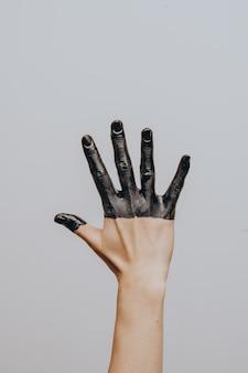 Main féminine élégante trempée dans de la peinture noire. isolé. geste.
