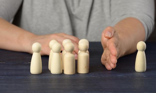 Main féminine entre les figures en bois d'hommes sur une surface bleue. le concept de querelle, de désaccord dans l'équipe. le besoin de réconciliation, de protection des opprimés