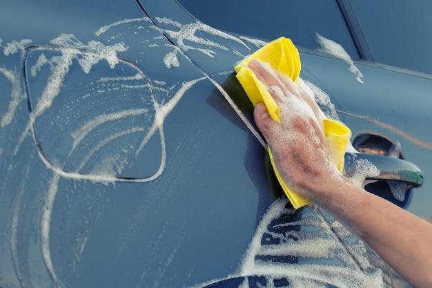 Main féminine avec une éponge jaune en mousse savonneuse lave la voiture