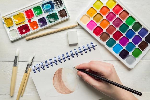 Main féminine esquissant la peinture à l'aquarelle. peintures et pinceaux aquarelles, vue de dessus. mise à plat artistique créative.