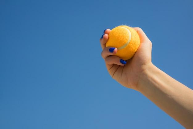 Main féminine est titulaire d'une balle de tennis orange vif sur fond de ciel bleu