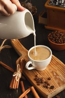Main féminine faisant le café du matin pour le petit déjeuner. lait versé dans l'espresso, gros plan. , tasse blanche et cannelle sur une vieille planche de bois rustique, espace de copie