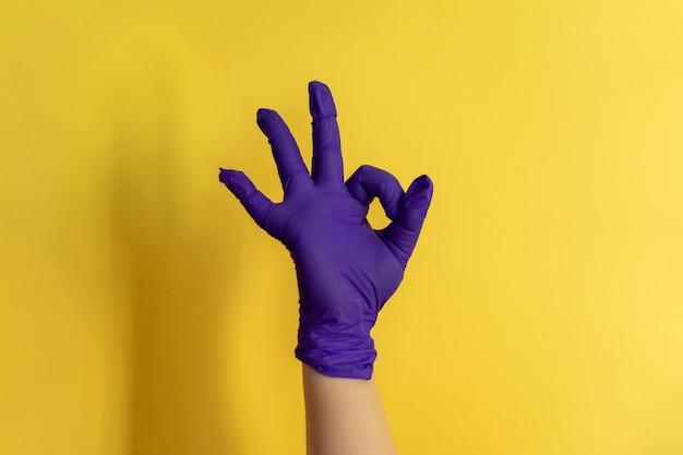 Main féminine en faux gant en latex montre différents gestes, nettoyage alternatif de la maison