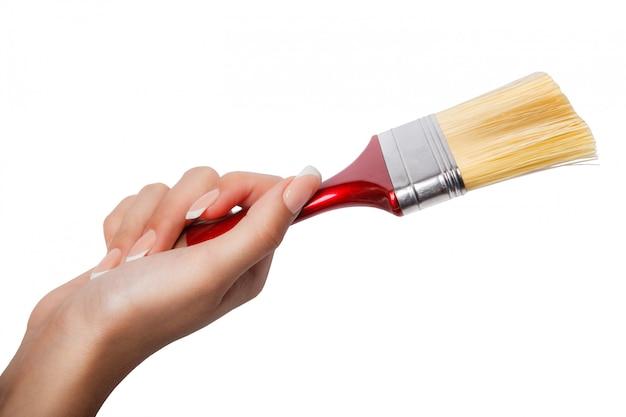 Une main féminine (femme) tenir un pinceau rouge isolé blanc, vue de dessus au studio.