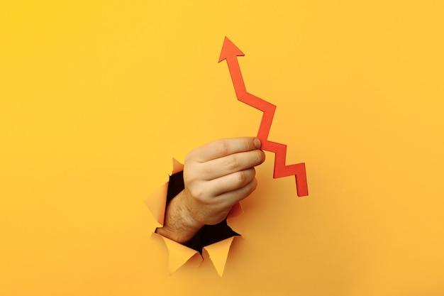 Main féminine avec une flèche rouge vers le haut à travers un concept d'entreprise de trou de papier jaune