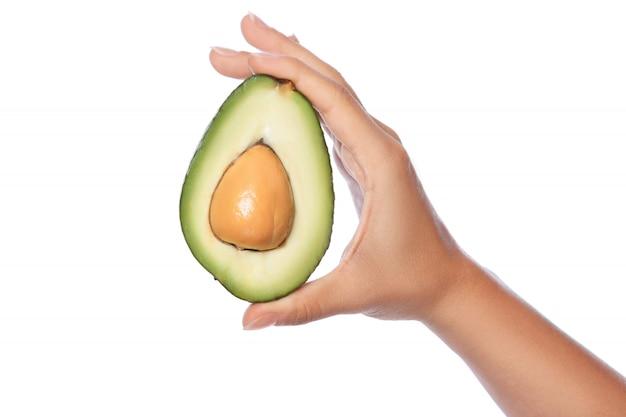 Main féminine avec des fruits frais d'avocat