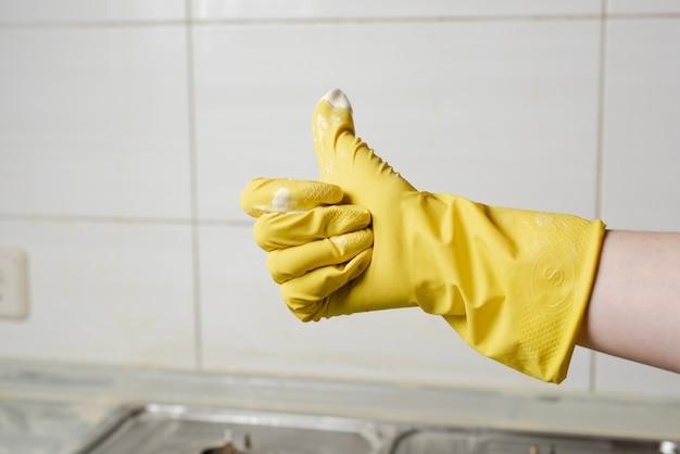 Main féminine en gant jaune montrant le pouce vers le haut