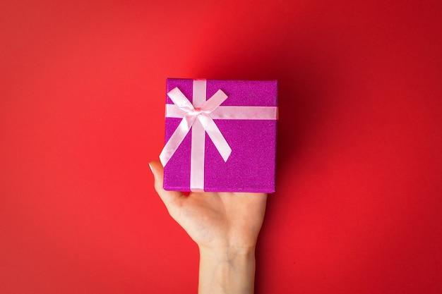 Main féminine gauche avec une boîte-cadeau sur un mur rouge. surprise entre les mains d'une fille.