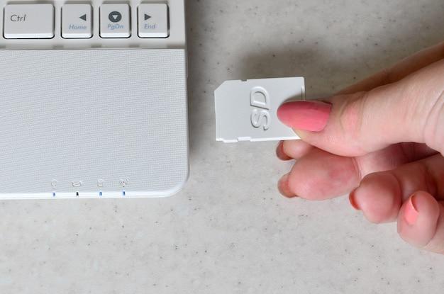Une main féminine insère une carte sd compacte blanche dans la mémoire correspondante.
