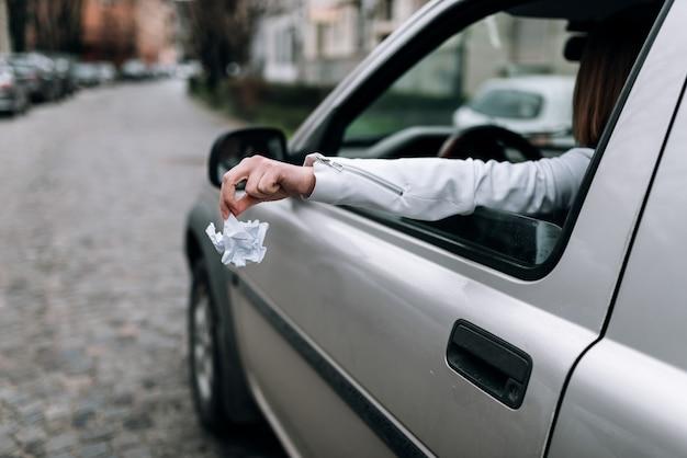 Main féminine jetant des ordures hors de la fenêtre de la voiture.