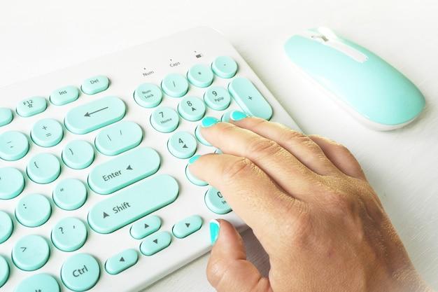 Main féminine avec manucure bleue sur un clavier blanc et bleu sur un tableau blanc.