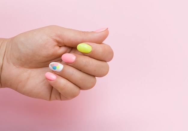 Main féminine avec manucure d'été avec crème glacée sur surface rose