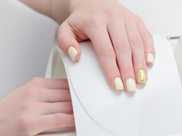 Main féminine avec manucure sur fond blanc