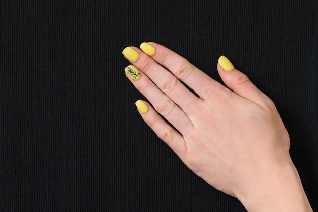 Main féminine avec manucure jaune sur un tissu noir.