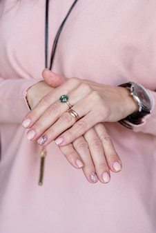 Main féminine avec manucure rose pastel
