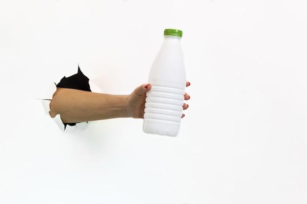 Une main féminine avec une manucure rouge dans un trou déchiré sur fond blanc tient une bouteille en plastique blanche