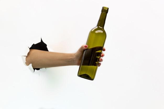 Une main féminine avec une manucure rouge dans un trou déchiré sur fond blanc tient une bouteille de vin.