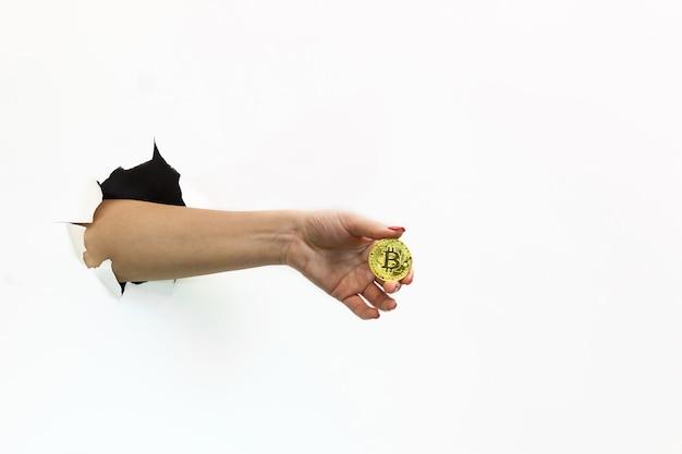 Une main féminine avec une manucure rouge dans un trou déchiré sur fond blanc tient une pièce d'or bitcoin.