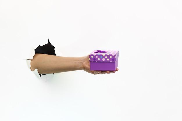 Une main féminine avec une manucure rouge à travers du papier blanc déchiré tient une banque d'alimentation. livre blanc déchiré à la main