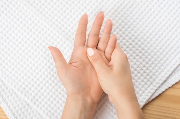 Une main féminine masse l'autre main allongée sur une serviette blanche avec la paume ouverte vers le haut. gros plan sur la main de la personne qui lui masse la main de la douleur dans un auto-massage sain d'accupression.