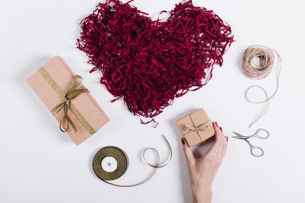 Une main féminine met des boîtes avec des cadeaux près d'un cœur décoratif rouge