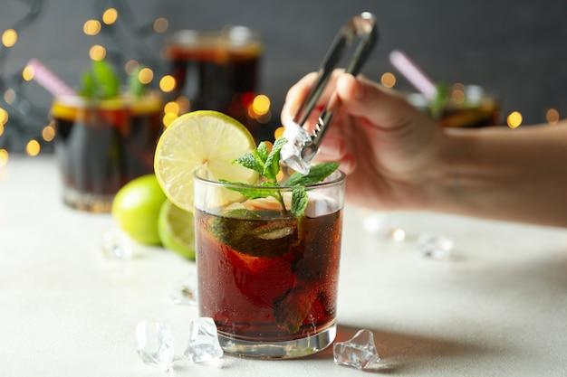 Une main féminine met de la glace dans un verre de cuba libre