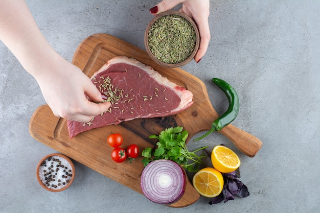 Main féminine mettant des herbes sur un morceau de viande crue placé sur une table en pierre.