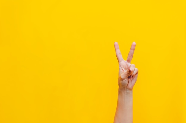 Main féminine montrant un geste de paix isolé sur un mur jaune de couleur vive
