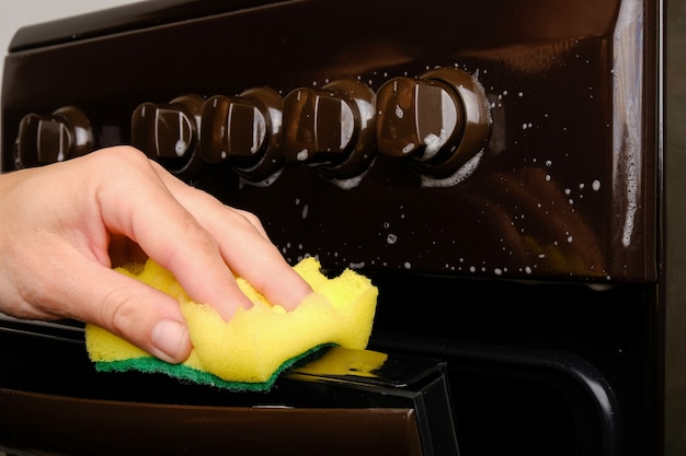 Une main féminine nettoie la cuisinière à gaz avec une éponge avec de la mousse blanche, nettoyant la surface. hygiène à la maison, électroménagers.