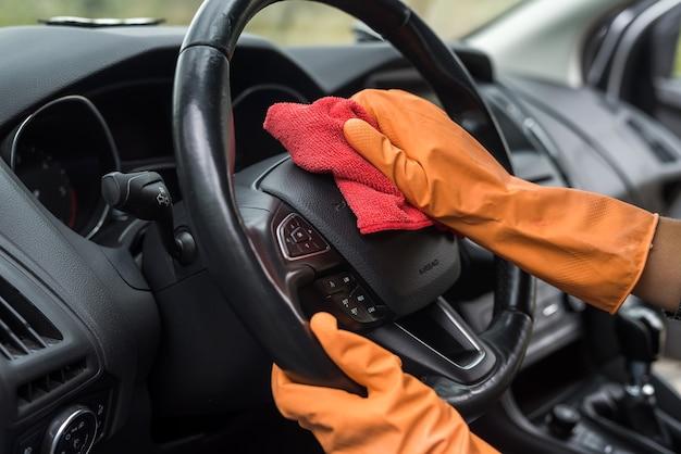 Main féminine nettoyant l'intérieur de sa voiture du coronavirus et de la pandémie avec du liquide désinfectant. laver le véhicule
